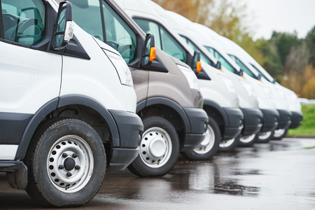 fleet: freight services. commercial delivery vans in row at transporting carrier shipping service company parking