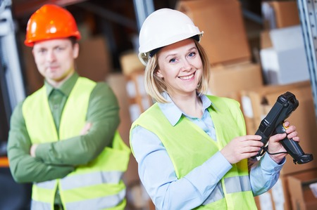 Male and female warehousing worker in storehouse with wireless barcode scanner. Warehouse Management System Stock Photo