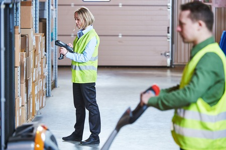 barcode scanner: Warehousing. workers using wireless barcode scanner and fork stacker. Warehouse Management System Stock Photo