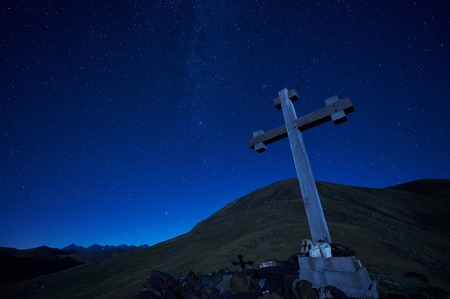 orthodoxy: cross sign on the top peak pass of caucasian mountain at night