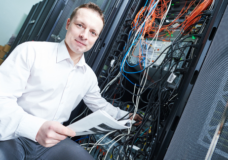 network server: network engineer  technician worker admin during server administration at data center room Stock Photo