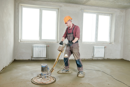finishing: construction worker walk behind power trowel machine during concrete floor wet grinding process by electrical grinder