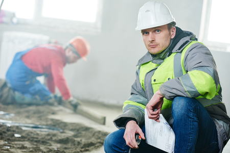 foreman: foreman builder and construction worker portrait in front of concrete floor covering in new indoor building flat apartment