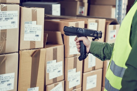 skladník pracovník pomocí bezdrátové čtečky čárových kódů. Warehouse Management System
