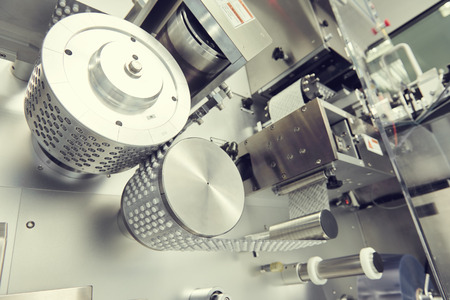 pharmaceutical plant: pharmaceutical medicine tablet pill production at pharmacy industry manufacture. Blistering packing machine