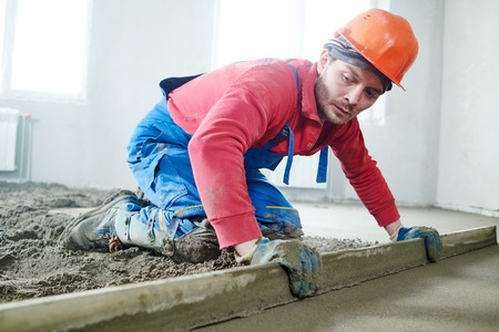builder worker screeding indoor cement floor with screed at construction site Stock Photo - 56647179