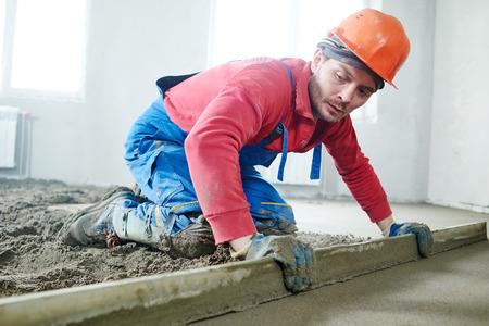 stavitel pracovník stěrka vnitřní cementové podlahy s potěrem na staveništi