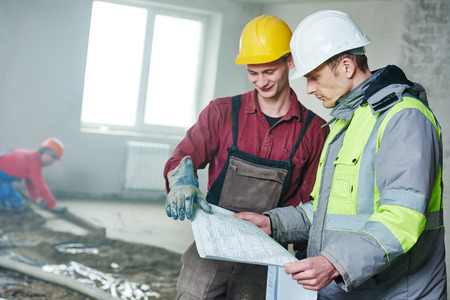 floor covering: foreman builder and construction worker with blueprint discussing floor covering in new building or repairing indoor flat apartment Stock Photo