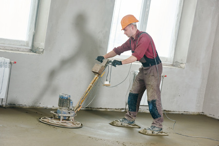 rennovation: construction worker walk behind power trowel machine during concrete floor wet grinding process by electrical grinder
