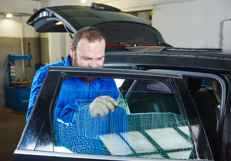 car glass: car tinting. Automobile mechanic technician applying foil on  window in repair garage workshop Stock Photo