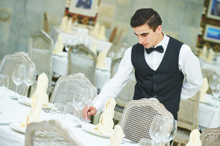dinner party: Catering service. young male waiter man serving banquet table with knife fork and glass at restaurant or cafe