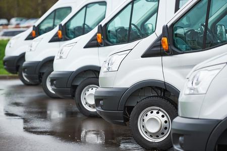 anuncio publicitario: servicios de transporte de mercancías. furgonetas de reparto comercial en fila en el estacionamiento de la compañía transportista que lleve servicio de envío