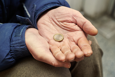 homeless person: Beggar people and human poverty. Male hands of homeless person with one euro charity in city street Stock Photo