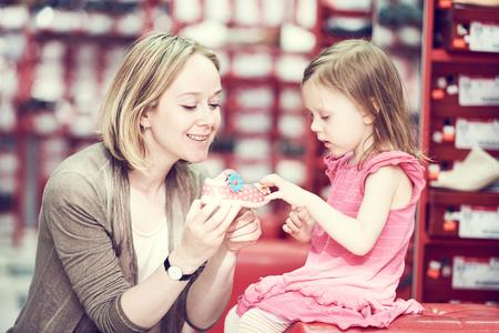 chaussure: achats de la famille. Jeune maman femme avec petite fille enfant fille choisir des chaussures de chaussures
