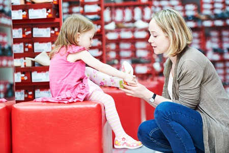 female child: Family shoe shopping. Young woman mother with little child girl daughter choosing footwear