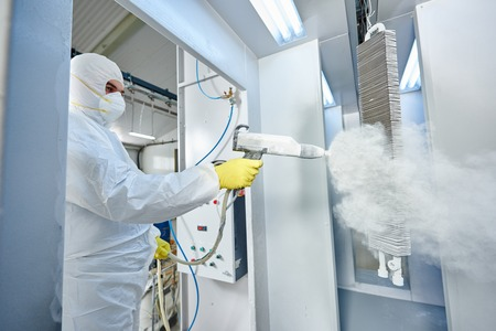 protective suit: industrial metal coating. Worker man in protective suit with gas mask spraying powder to steel finished parts in painting chamber