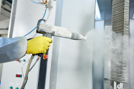 Industriemetallbeschichtung. Worker Mann im Schutzanzug mit Gasmaske Spritzpulver auf Stahlfertigteile in der Malerei Kammer