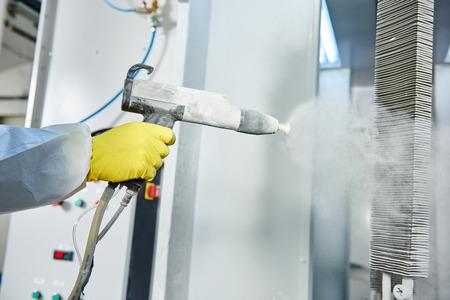 průmyslové lakování kovů. Pracovník muž v ochranném obleku s plynovou maskou nástřikem prášku na ocelové hotových dílů v lakovně komoře