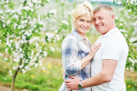 flowering: Happy adult young couple in love. Blossoming apple tree garden outdoors.