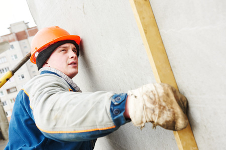 rigger: Construction worker. Builder examining concrete wall with level at building area Stock Photo