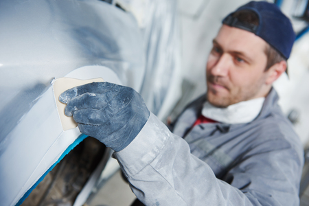 Auto body repairs. Repairman mechanic worker plastering automobile car body by plaster in garage workshop Stockfoto