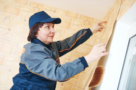 개조 또는 개조. 아파트 벽에 적용 벽지를 설치하는 여성의 종이 옷걸이 노동자