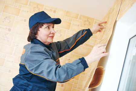 refurbishment: refurbishment or renovation. female paper hanger worker installing wallpaper applying them to apartments wall Stock Photo