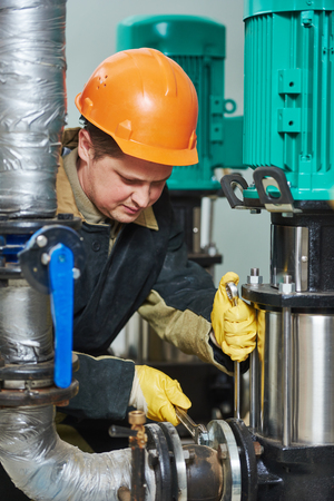 maintenance fitter: technician worker of heating system in boiler room Stock Photo