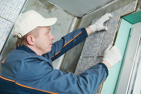 work worker: industrial tiler builder worker installing wall tile at repair renovation work