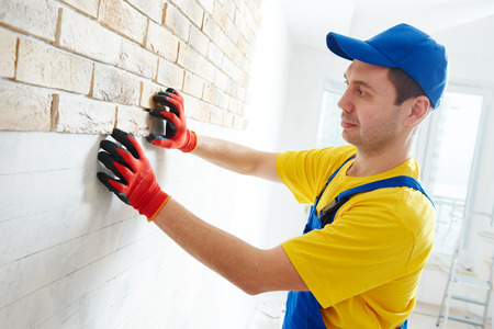 facing a wall: interior wall facing decorating work with brick veneer installing by professional construction worker bricklayer at home indoors