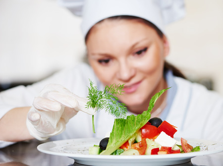 female cook chef decorating garnishing prepared salad food dish on the plate in restaurant commercial kitchen