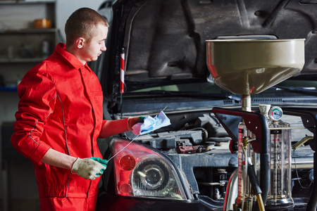 scheduled replacement: Motor oil replacement. Auto mechanic replacing and checking fresh oil at engine during maintenance in garage repair service station
