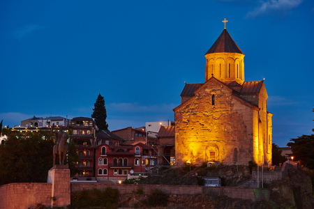 sacred trinity: Metekhi orthodox monastery and church at sunset. Touristic landmark in Tbilisi Georgia Stock Photo