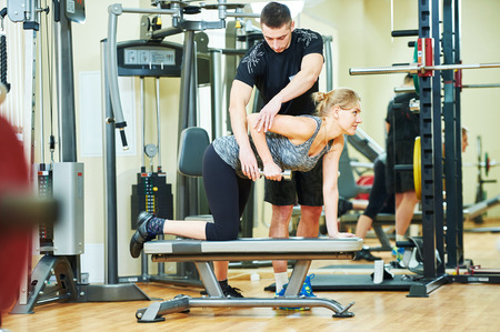 programm: Fitness training. Personal trainer helping woman working with dumbbells in gym Stock Photo