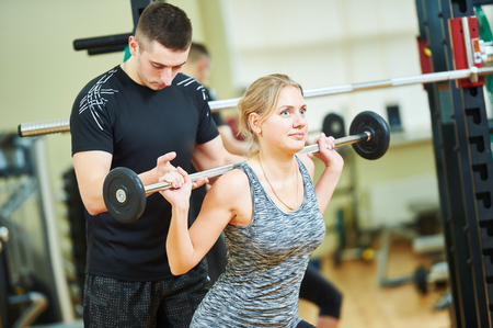 programm: Personal trainer helping woman working with barbell weght