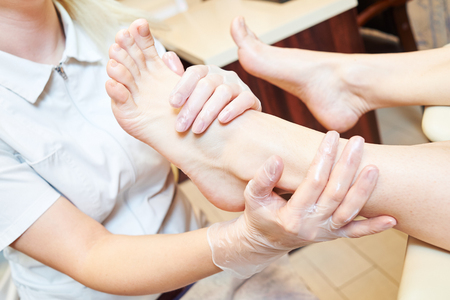 woman foot: Young woman is getting foot massage before pedicure procedure in beauty salon Stock Photo