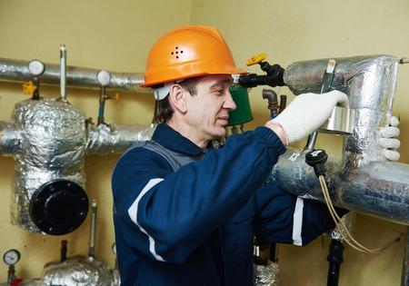 Isolation thermique. travailleur de la chaudière d'isolation des tuyaux du système de chauffage avec une feuille d'aluminium Banque d'images - 57001009