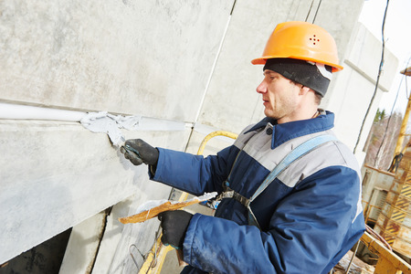 parget: Facade plasterer worker sealing concrete slab joint seam with insulation material and putty mastic at outdoor building wall