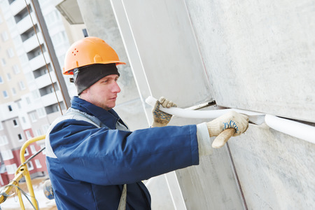 Facade plasterer worker sealing concrete slab joint seam with insulation material and putty mastic at outdoor building wall
