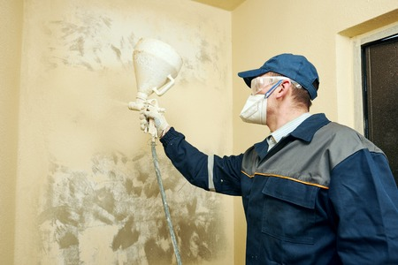 priming paint: painter painting indoors wall by spraying yellow paint