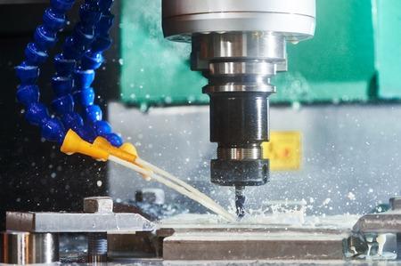 Frézování metalworking proces. Přesné průmyslové CNC obrábění detailu kovu odříznutím mlýn ve výrobním závodě