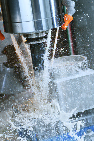 automated tooling: Milling metalworking process. Industrial CNC machining of metal detail by cutting end-tooth vertical mill at factory Stock Photo