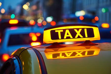 Geel taxi teken op taxi auto 's avonds of' s nachts in de stadsstraat
