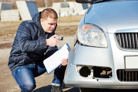 Verzekeringsagent opnemen schade na auto-ongeluk tijdens het inspecteren beschadigde auto op claimformulier Stockfoto