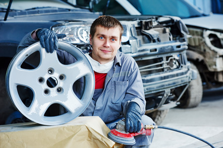 plasterer: Auto repair mechanic worker with light alloy car wheel disk rim during refurbish at garage service station.