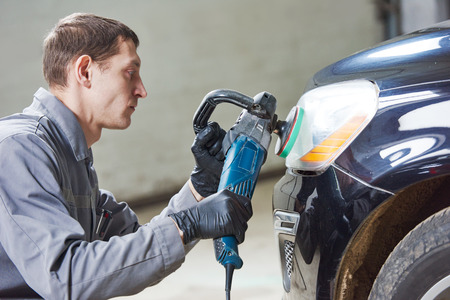 buffing: Auto body repairs. Mechanic worker burnish and polishing automobile car headlight by buffing grinding machine in garage workshop. Toned
