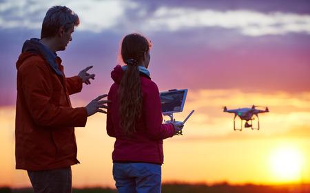 Hombre con aviones no tripulados que operan niño volando o flotando por control remoto en la puesta del sol.