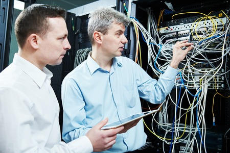 two network support engineers technician workers admin during server administration at data center room