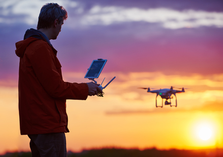 maneuvering: Man operating drone flying or hovering by remote control in sunset.