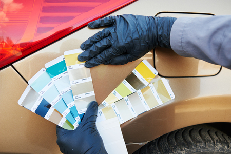 paint samples: auto colour matching. colourist man selecting color of car at automobile repair and renew service station with paint samples